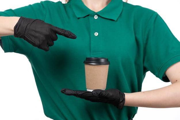 Un giovane corriere femminile di vista frontale in guanti neri uniformi verdi e tazza di caffè nera della tenuta della maschera