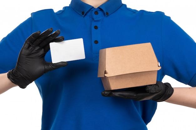 Un giovane corriere femminile di vista frontale in maschera nera uniforme blu e guanti che tengono il pacchetto di consegna dell'alimento