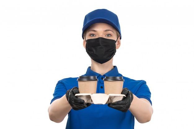 Un giovane corriere femminile di vista frontale in maschera nera uniforme blu e guanti che tengono le tazze di caffè