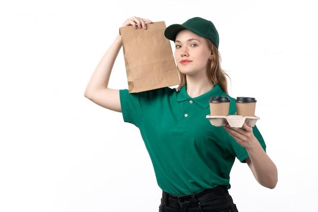 Un giovane corriere femminile di vista frontale in pacchetto dell'alimento e tazze di caffè sorridenti uniformi verdi della tenuta