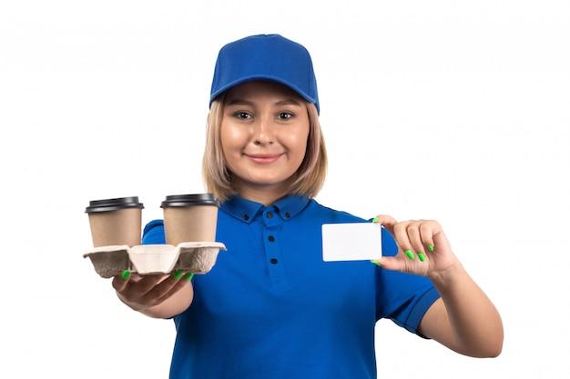 Un giovane corriere femminile di vista frontale in tazze di caffè della tenuta dell'uniforme blu e carta bianca