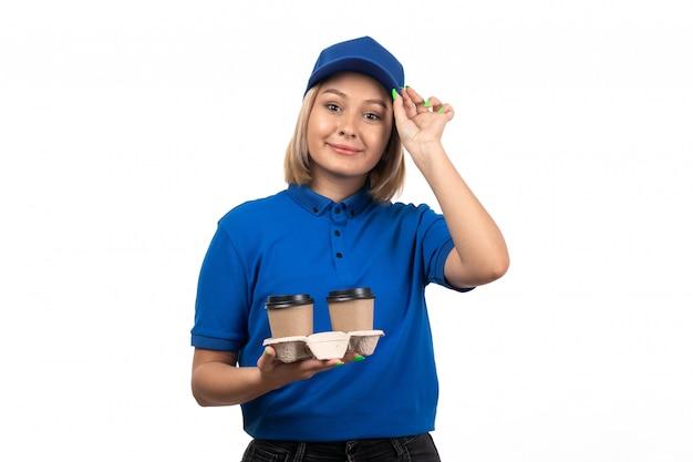 Un giovane corriere femminile di vista frontale in tazze di caffè della tenuta dell'uniforme blu