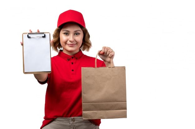 Un giovane corriere femminile di vista frontale nel pacchetto di consegna della tenuta del cappuccio rosso della camicia rossa e nel sorridere del blocco note