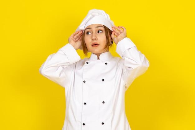 Un giovane cuoco femmina di vista frontale in abito bianco cuoco e berretto bianco che fissa il suo vestito sul giallo
