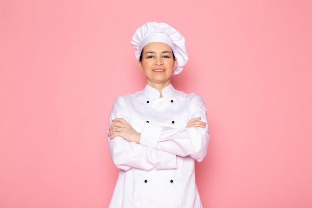 Un giovane cuoco femmina di vista frontale nel sorridere bianco del vestito bianco del vestito del cuoco felice