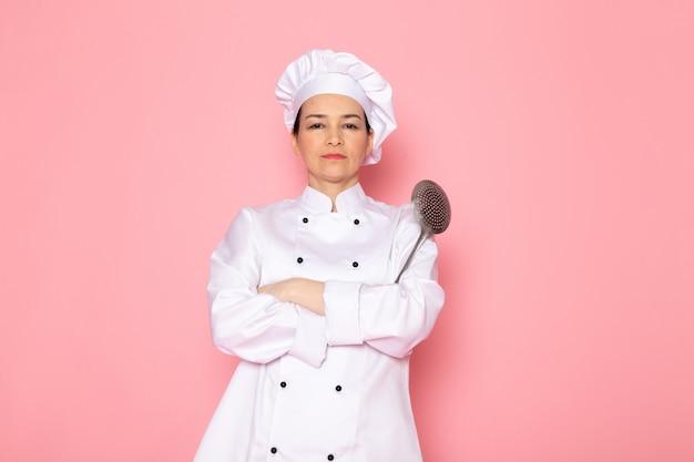 Un giovane cuoco femminile di vista frontale in protezione bianca del vestito bianco del cuoco che propone tenendo espressione rigorosa del grande cucchiaio d'argento