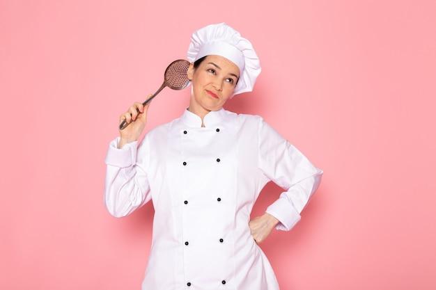 Un giovane cuoco femminile di vista frontale in protezione bianca del vestito bianco del cuoco che propone tenendo l'espressione esitante del grande cucchiaio d'argento