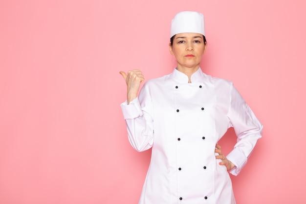 Un giovane cuoco femminile di vista frontale in protezione bianca del vestito del cuoco bianco che propone sguardo serio dispiaciuto con l'espressione della mano