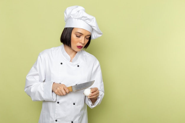Un giovane cuoco femminile di vista frontale in vestito bianco del cuoco e berretto che rompe l'uovo sulla parete verde