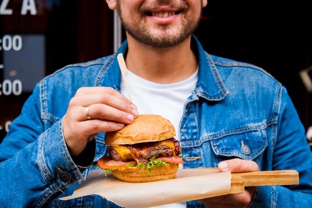 Un giovane cuoco maschio tiene in mano un hamburger fatto a mano con carne e verdure.