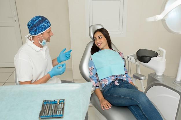 Un giovane dentista maschio e un paziente femminile felice. scena di stile di vita dell'ufficio del dentista. pratica medica. assistenza sanitaria al paziente
