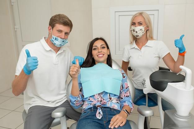 Un giovane dentista maschio, il suo assistente e felice paziente femminile pollice in alto. scena di stile di vita dell'ufficio del dentista. pratica medica. assistenza sanitaria al paziente.