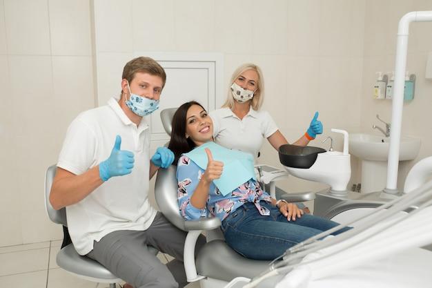 Un giovane dentista maschio, il suo assistente e felice paziente femminile pollice in alto