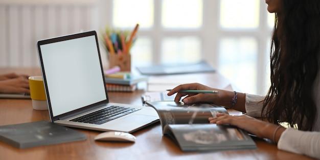 Un giovane designer sta lavorando con un computer portatile bianco schermo vuoto alla scrivania in legno.