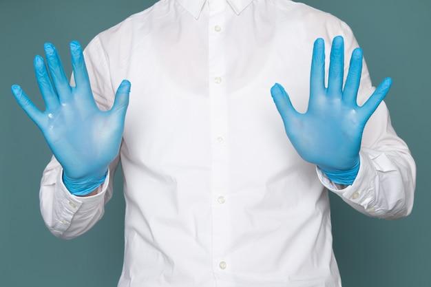 Un giovane di vista frontale che mostra le sue mani con i guanti blu sullo spazio blu