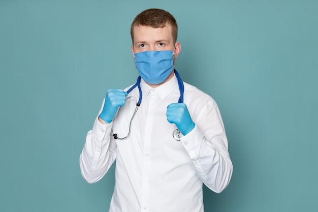 Un giovane di vista frontale in camicia bianca e guanti blu con maschera blu sullo spazio blu