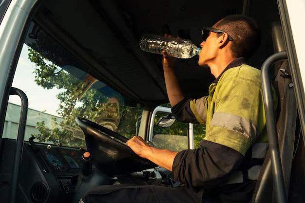 Un giovane dice che va tutto bene un camion dentro la cabina con i vestiti di sicurezza