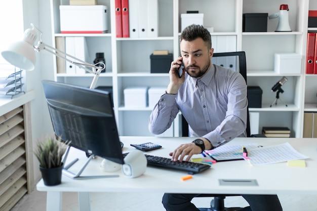 Un giovane è seduto in ufficio, parla al telefono e lavora al computer.