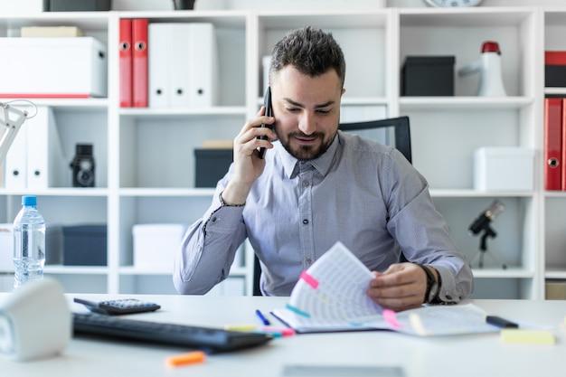 Un giovane è seduto in ufficio, parla al telefono e lavora con i documenti.