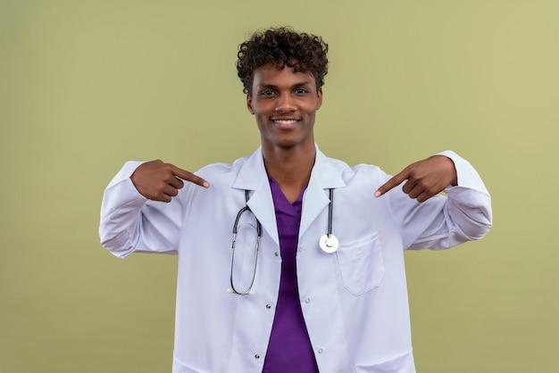Un giovane eccitato bell'uomo di carnagione scura con i capelli ricci che indossa camice bianco con uno stetoscopio rivolto a se stesso con le dita indice su uno spazio verde