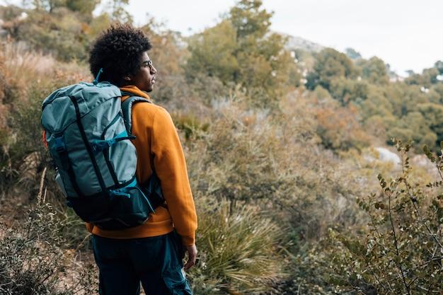 Un giovane escursionista maschio africano che fa un'escursione con lo zaino