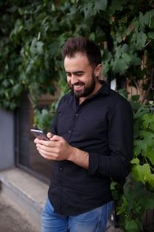 Un giovane figo usa uno smartphone. hipster con la barba sta scrivendo un messaggio sul suo telefono cellulare. copia spazio.