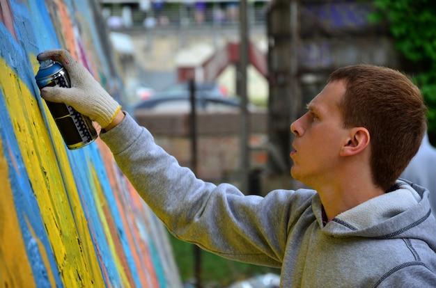 Un giovane graffitista dai capelli rossi dipinge un nuovo graffito sul muro. foto del processo di disegnare un graffito su un primo piano del muro.