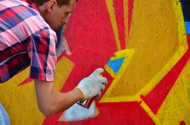Un giovane graffitista dai capelli rossi dipinge un nuovo graffito sul muro.
