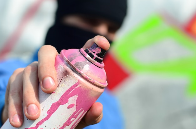 Un giovane graffitista in giacca blu e maschera nera regge