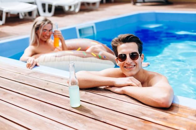 Un giovane guarda fuori dalla piscina, appoggiandosi sulla riva della piscina, con una bottiglia da bere vicino a lui