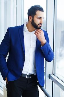 Un giovane imprenditore di successo si trova vicino alla finestra con un'espressione concepita del viso