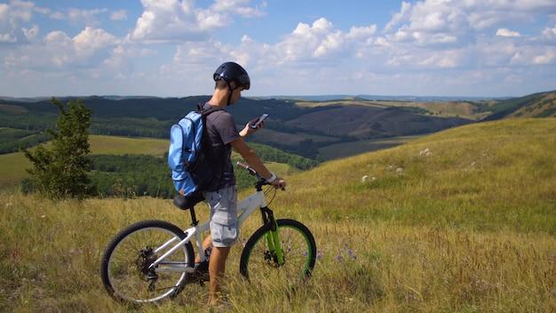 Un giovane in bicicletta è guidato dal terreno usando una mappa sul suo cellulare