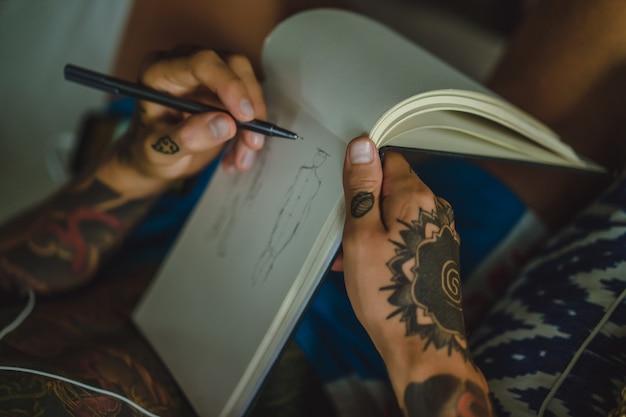 Un giovane in tatuaggi che indossa le cuffie ascolta musica e disegna in un taccuino.