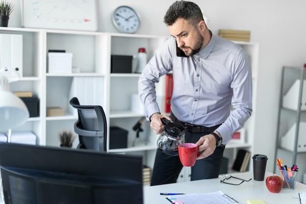 Un giovane in ufficio è in piedi vicino al tavolo, tiene il telefono con la spalla, guarda il monitor e versa il caffè nella tazza.