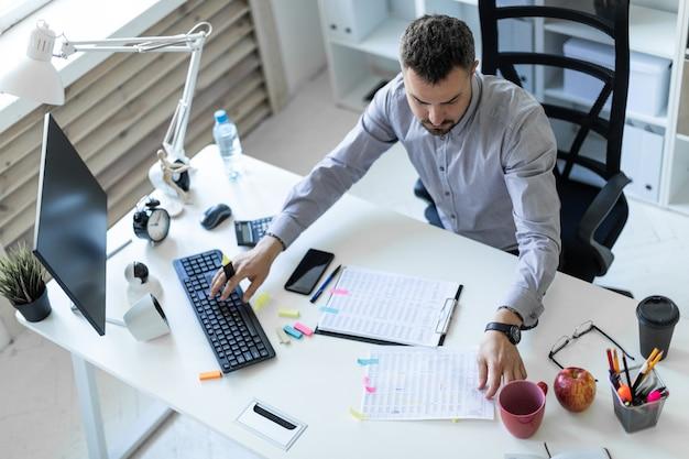 Un giovane in ufficio è seduto a un tavolo, tiene in mano un pennarello e lavora con documenti e un computer.