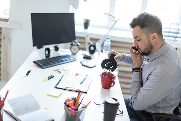 Un giovane in ufficio si siede a un tavolo, parla al telefono e versa il caffè in una tazza.
