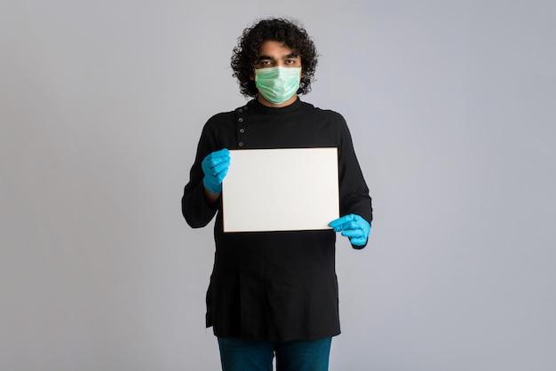 Un giovane in una mascherina medica che tiene e che mostra una scheda in bianco