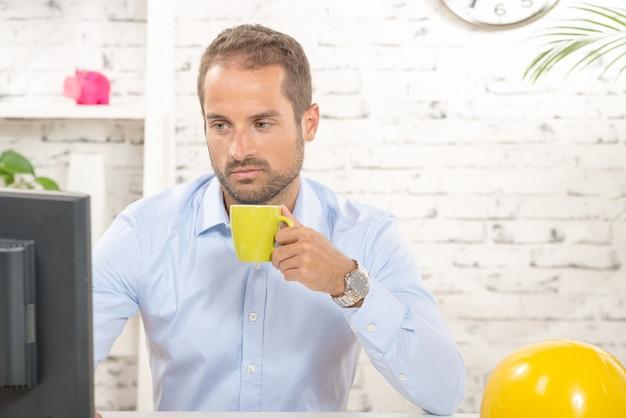 Un giovane ingegnere che beve caffè durante la pausa