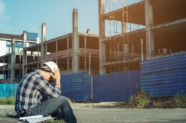 Un giovane ingegnere è seduto stressato. perché il progetto di costruzione è stato annullato.
