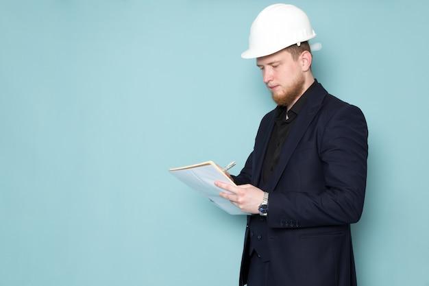 Un giovane maschio attraente di vista frontale con la barba in vestito moderno classico scuro nero nel casco bianco della costruzione che annota le note sullo spazio blu