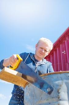 Un giovane maschio biondo in un maglione blu e jeans sega una barra di legno contro un cielo blu.