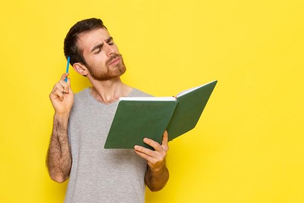 Un giovane maschio di vista frontale in libro di lettura grigio della maglietta con l'espressione di pensiero sul modello di colore di emozione di espressione dell'uomo della parete gialla