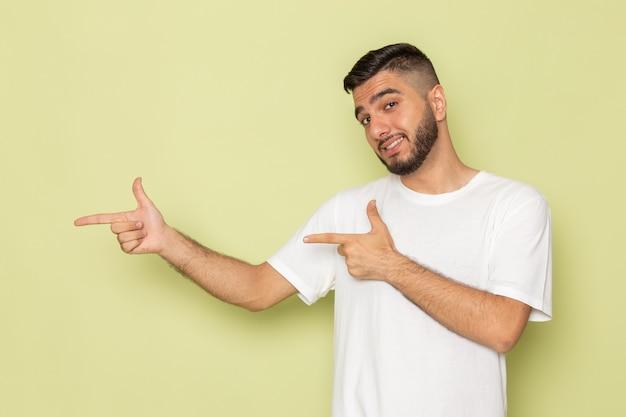 Un giovane maschio di vista frontale in maglietta bianca che posa con il sorriso
