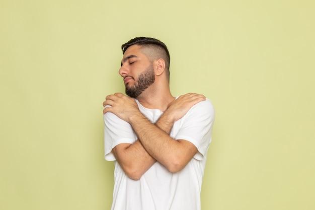 Un giovane maschio di vista frontale in maglietta bianca che posa e che si abbraccia