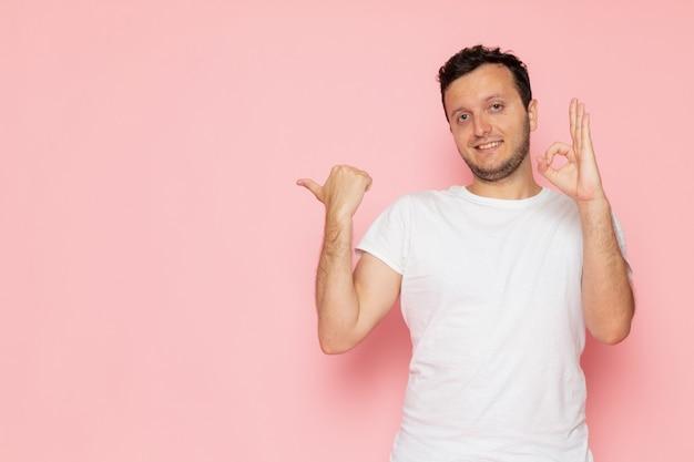 Un giovane maschio di vista frontale in maglietta bianca che posa sorridendo e mostrando il segno giusto