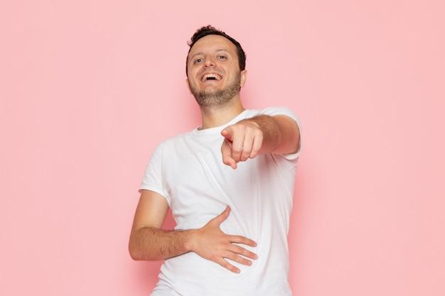 Un giovane maschio di vista frontale in maglietta bianca che ride ad alta voce