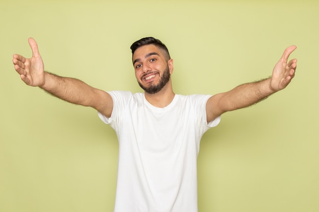Un giovane maschio di vista frontale in maglietta bianca che sorride con le armi sparse
