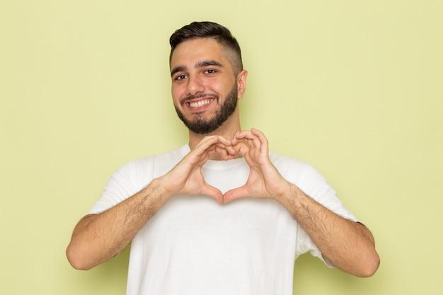 Un giovane maschio di vista frontale in maglietta bianca che sorride e che mostra il segno di amore