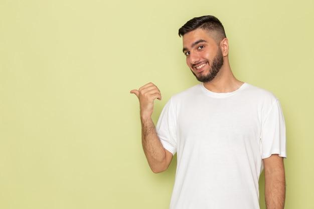 Un giovane maschio di vista frontale in maglietta bianca che sorride e che posa