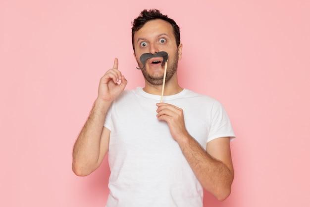 Un giovane maschio di vista frontale in maglietta bianca che tiene i baffi falsi sulla posa rosa di emozione di colore dell'uomo dello scrittorio